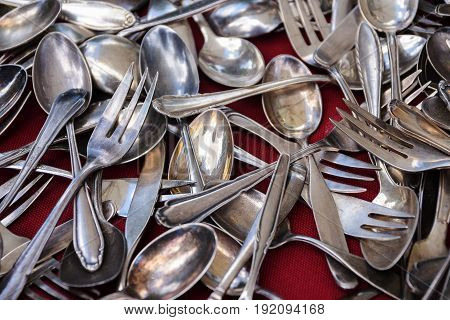 Old silver cutlery hrown on a background of red fabric selected focus narrow depth of field