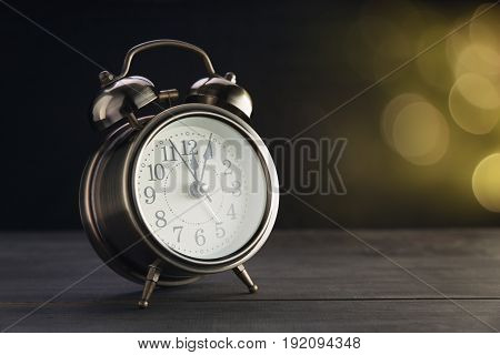 Bokeh background with retro alarm clock on table.