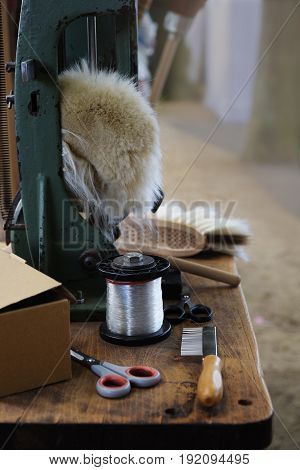 Tools of a brushmaker and broom binder as scissors yarn comb bunch hair and bristles at a craft market vertical selective focus narrow depth of field