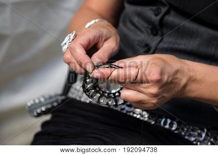 Creative hobby women's hands making objects from yarn and metal can stay-tabs with a crochet hook such as belts bags and jewelery copy space selected focus narrow depth of field