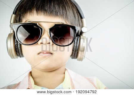 Seriously looking boy with sunglasses is listening to Music on his headphone