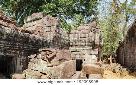 The ancient ruins of the Preah Khan Temple in Siem Reap, Cambodia. A pile of old stones on a tourist road in the foreground. Ancient Khmer architecture, famous Cambodian landmark, World Heritage