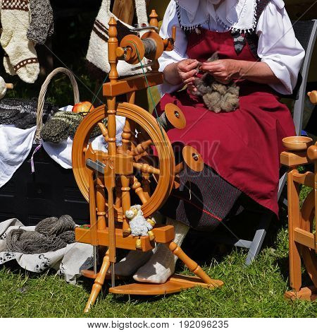 woman with wool at the traditional spinning wheel on an medieval craft market