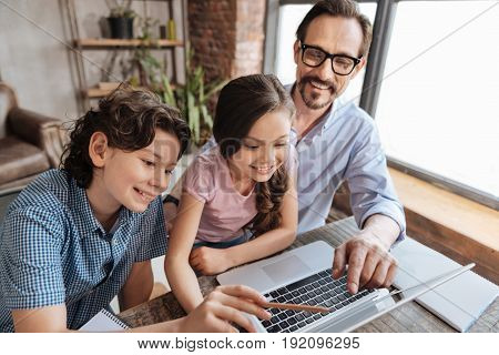 Look here. Handsome young father and his children sitting in front of a laptop, and father with his son pointing at something on the screen, showing it to the daughter