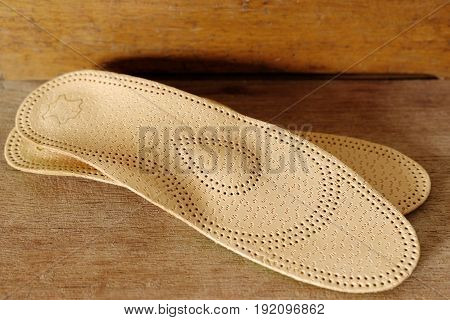 Orthopedic arch support made from leather on a wooden ground