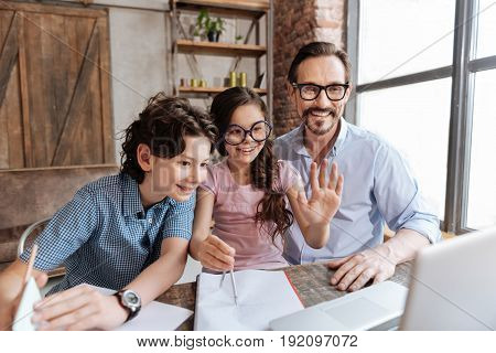 Hello there. Joyful single-parent family making a video call to their relatives while a cute little girl waving hello at the web camera