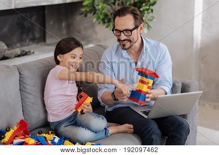 Nice idea. Handsome young father holding a house built with an erector set and watching an erector set assembling tutorial with his daughter while she pointing at the laptop with excitement