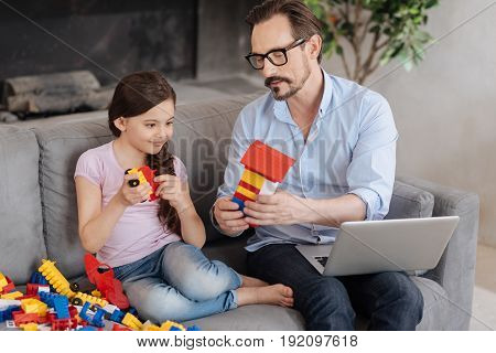 poster of Look what I have. Pleasant young father sitting on the sofa and showing an erector set house to his beloved daughter while she holding a car model and looking at the house with smile
