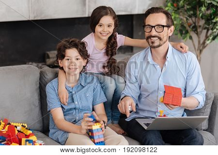 Sweet hugs. Gorgeous little girl sitting on the back of sofa and hugging her dear father and brother holding erector set pieces