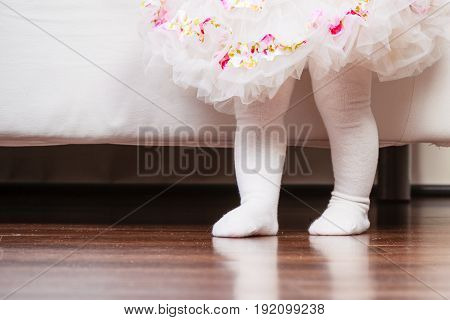 Feet Of Baby Girl In Dress