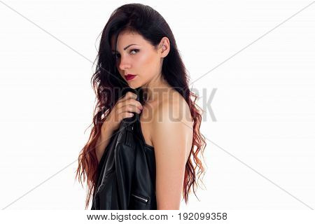 beautiful brunette woman hide her breasts beahind a leather jacket isolated on white background