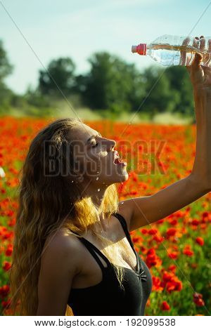 water in plastic bottle at girl with long curly hair in flower field of red poppy summer drug and intoxication opium refreshment and relax sport and fitness healthcare and thirst youth