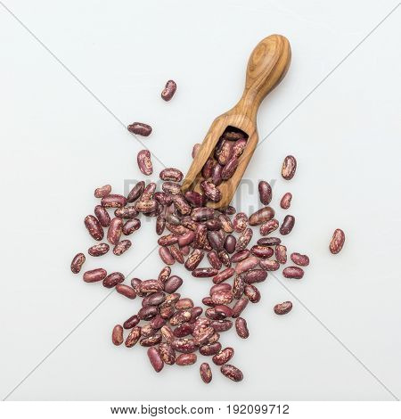 Organic red beans and olive wood scoop on whie background. Top view