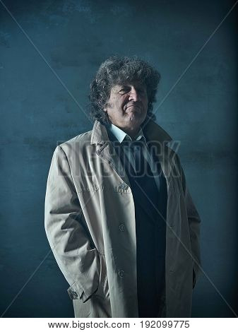 The senior man in cloak as detective or mafia boss. Studio shot on gray in retro stile
