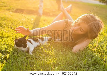 Pets and owner concept - Beautiful girl playing with a cat in the grass