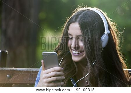 She Listens To Music And Holds A Mobile Phone In Her Hand