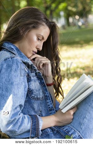 Young Woman Relaxes In Nature And Carefully Reads The Book