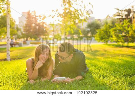 summer, love and people concept - close up of happy teenage couple lying on grass with earphones and listening to music