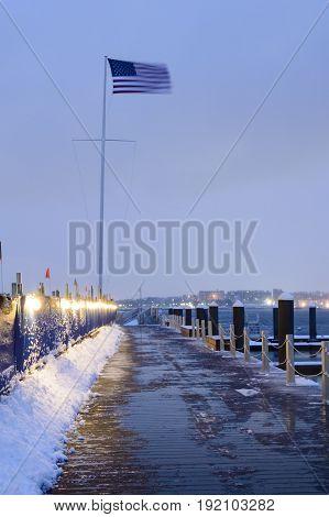 Fierce wind straightens American flag on winter morning near construction project along Fan Pier in South Boston