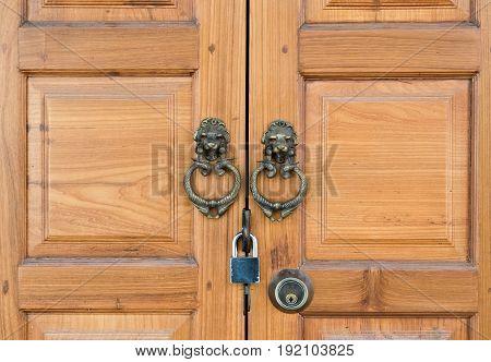 wooden door with metal handle and padlock