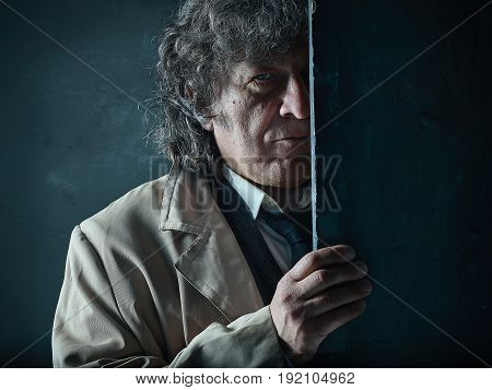 The senior man in cloak as detective or mafia boss. Studio shot on gray in retro stile. The male face close up