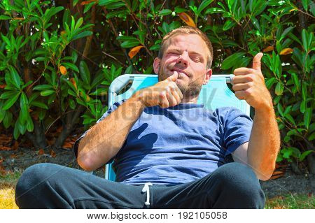 Young man sitting in a deck chair and holding a thumb up.