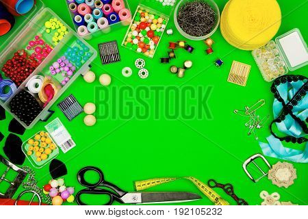 Sewing kit isolated on green background: scissors measuring tape beads ribbons sewing spools pins and needles.