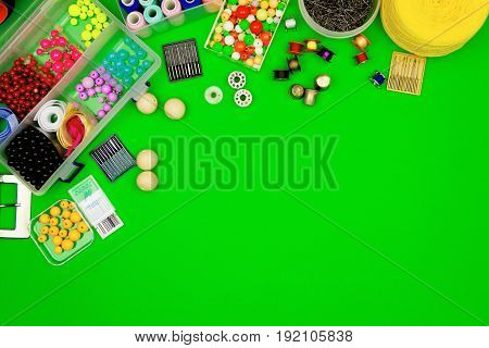 Sewing kit isolated on green background: beads ribbons sewing spools pins and needles.