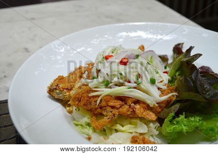 Deep fried soft shell crab with spicy salad in white dish - Thai cuisine