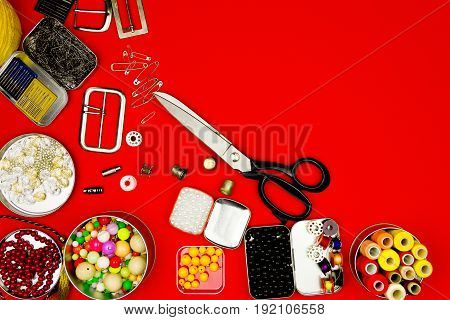 Sewing kit isolated on red background: scissorsbeads ribbons sewing spools pins and needles.