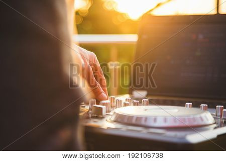 Dj mixing music outdoor. DJ's hand mix the sound on the control panel