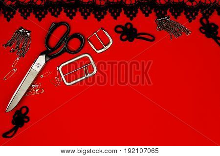 Sewing kit isolated on red background: scissors pins accessories metal buckles black frill