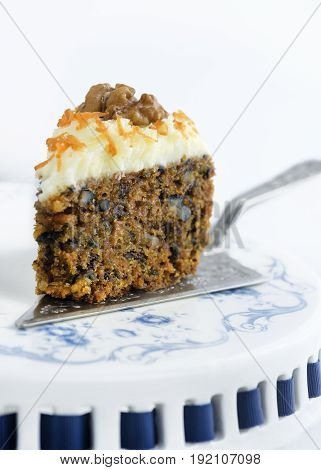 portion of moist carrot cake with nuts on a sliver cake-slice on a blue and white cake-stand, white background, room for copy space top and base