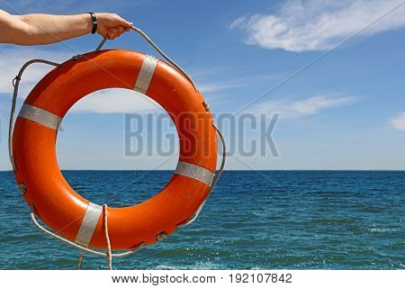 Man hand holding plastic orange color lifebuoy ring over blue sea water and clear sky close up low angle view