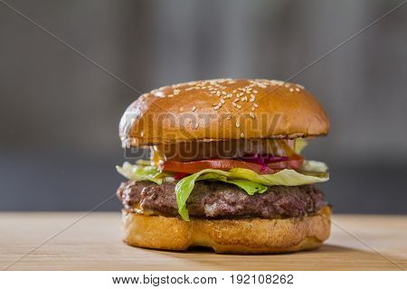 A large tasty burger on table, in a cafe