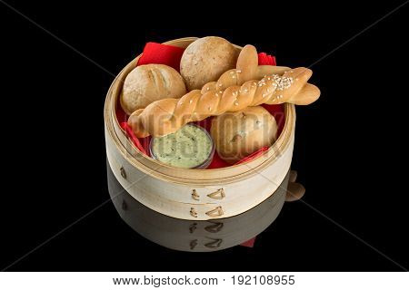 Bread basket with butter on a black background with reflection