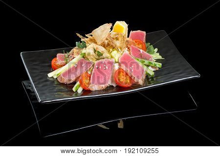 Salad with tuna on a black plate. Black background with reflection.