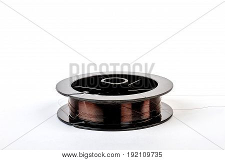 Copper wire on black reel. Copper wire spool, white background.