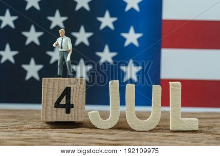 Independence day USA with miniature businessman standing on wooden cube number 4 and alphabets JUL and United State national flag in the background.