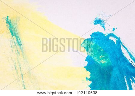 Macro shot of abstract hand drawn blue and yellow watercolor paints background