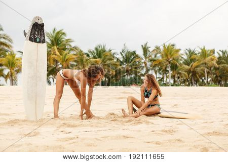Two Beautiful Surfer Girls Do A Warm-up At The Beach.