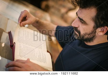 Curious Man Reading Old Book In His Library At Home