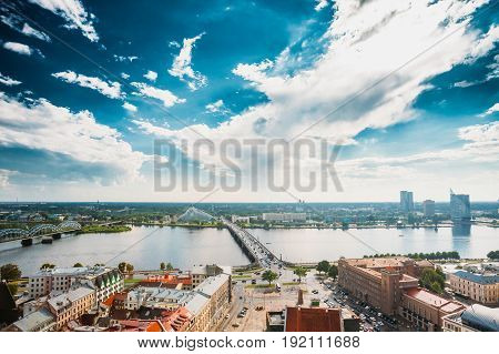 Riga, Latvia. Traffic On Akmens Tilts - Stone Bridge Street In Summer Day. Top View, Aerial View Of National Library Building, Named Castle of Light Or Gaismas Pils. Famous Landmark On Daugava Bank