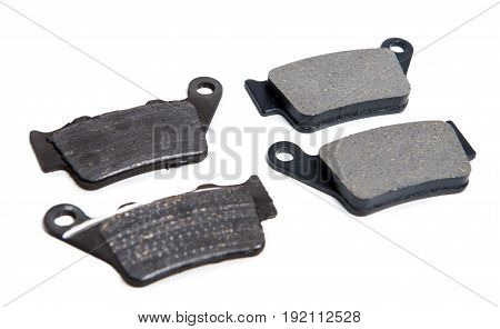 New and used brake pads for a motorcycle on white