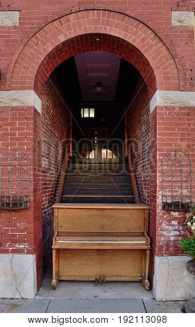 An old upright piano stands in the doorway of a brick building.