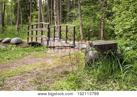 Simple wooden bench is in the forest trails in the park. In the background a small bridge over a stream.