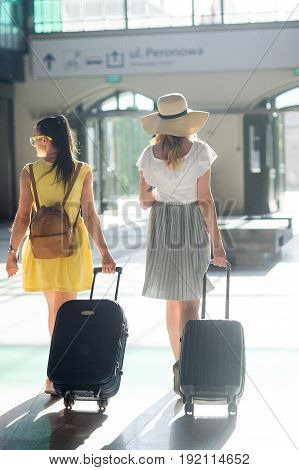 Two young tourists at the station. In hands at girls suitcases tickets passports. Summer tourism. View from a back.