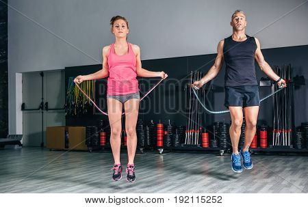 Young couple doing exercises with jumping ropes in sports center