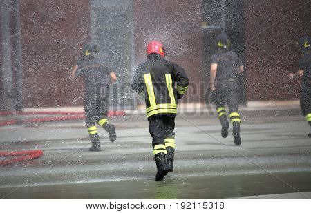 Firefighters Run Under The Splashes Of Water During Fire Extingu