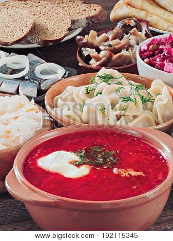 Perspective iew of wooden table with dishes of russian cuisine - borscht, pelmeni, herring, marinated mushrooms, , vinaigrette, sauerkraut, rye bread, pancakes. Vertical